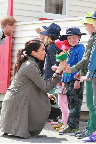 Harry and Meghan greeting some small children.