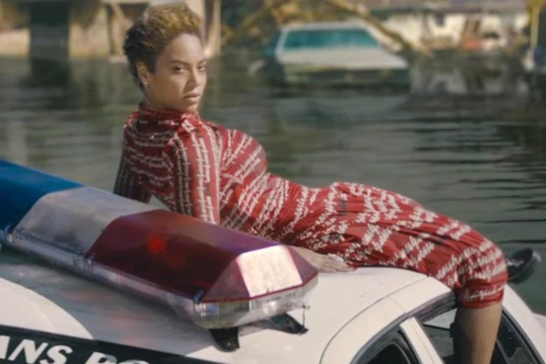 "In a still from the ""Formation"" video, Beyoncé reclines on a police car floating in floodwaters."