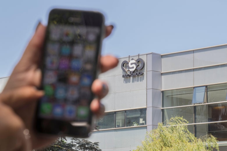 """An Israeli woman uses her iPhone in front of the building housing the Israeli NSO group, on August 28, 2016, in Herzliya, near Tel Aviv. Lookout and Citizen Lab worked with Apple on an iOS patch to defend against what was called """"Trident"""" because of its triad of attack methods, the researchers said in a joint blog post. Trident is used in spyware referred to as Pegasus, which a Citizen Lab investigation showed was made by an Israel-based organization called NSO Group. (Photo by JACK GUEZ / AFP) (Photo by JACK GUEZ/AFP via Getty Images)"""