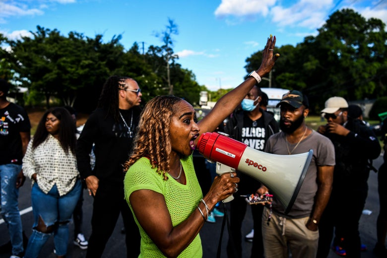 A woman holds up her first while speaking into a megaphone at a protest.