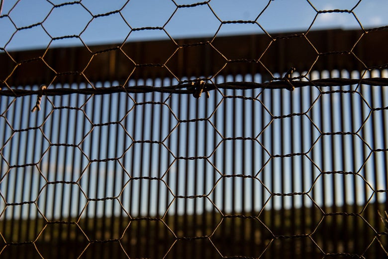 Blue sky and a sunny landscape show through a series of barriers, in ever-increasing focus: the slats of the United States border wall, in front of which is a strand of barbed wire, in front of which is a mesh of chicken wire.