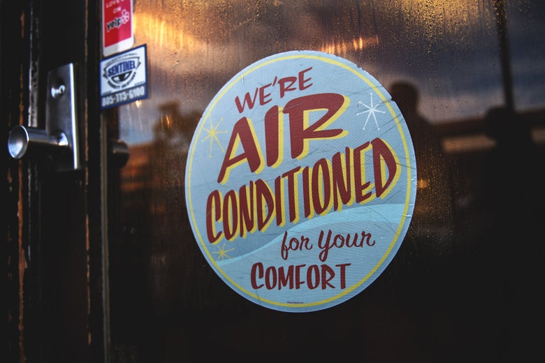 "A sign on a door says ""We're air conditioned for your comfort."""