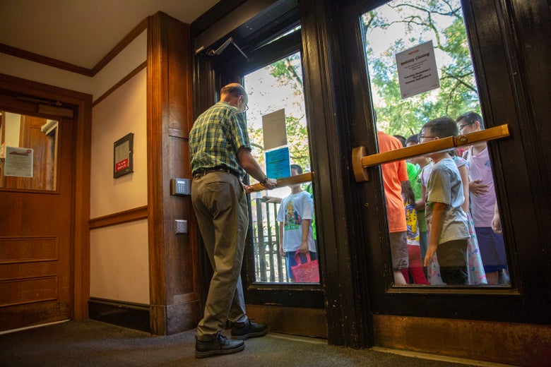 A librarian opens the doors of the library to children waiting outside.