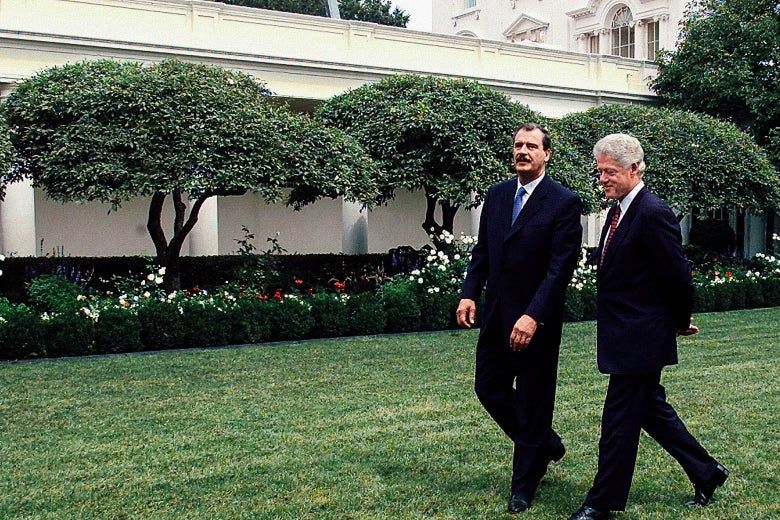 Bill Clinton walks with Vicente Fox through the White House Rose Garden.