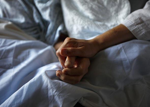A woman holds the hand of her mother who is dying from cancer during her final hours at a palliative care hospital in Winnipeg July 24, 2010.