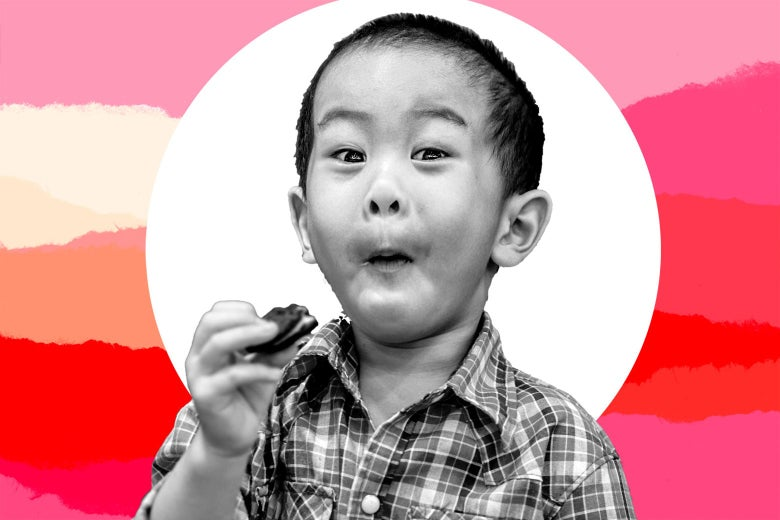 A young boy with wide eyes and an open mouth looking delighted while eating a cookie.