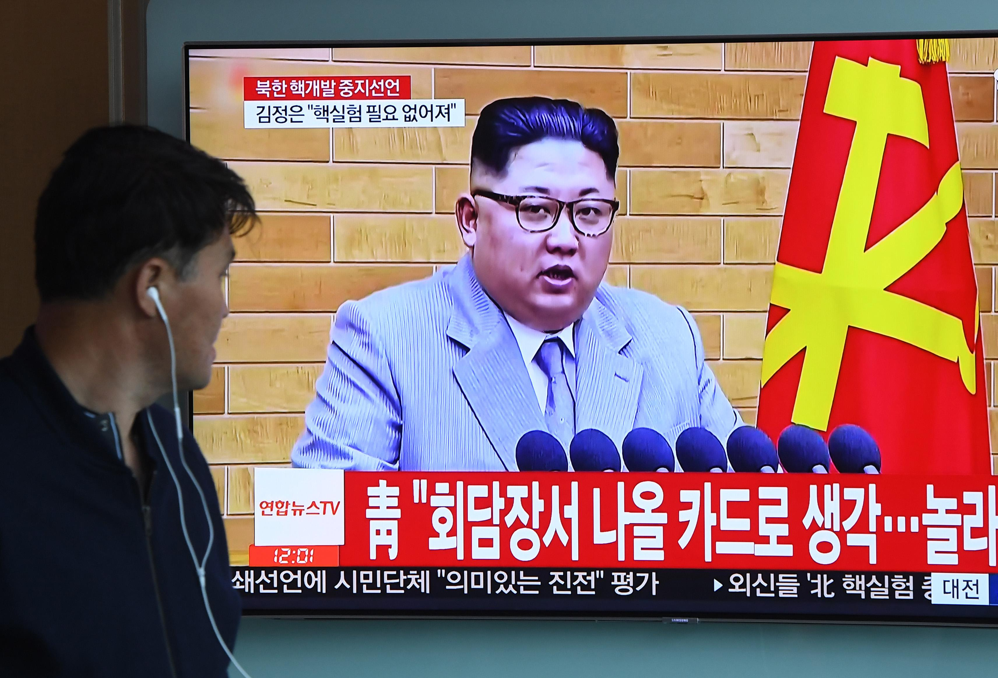 A man watches a television news showing a file footage of North Korean leader Kim Jong Un, at a railway station in Seoul on April 21, 2018.