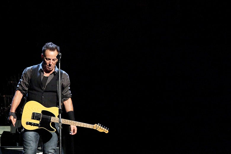Bruce Springsteen onstage with a guitar strapped around him.