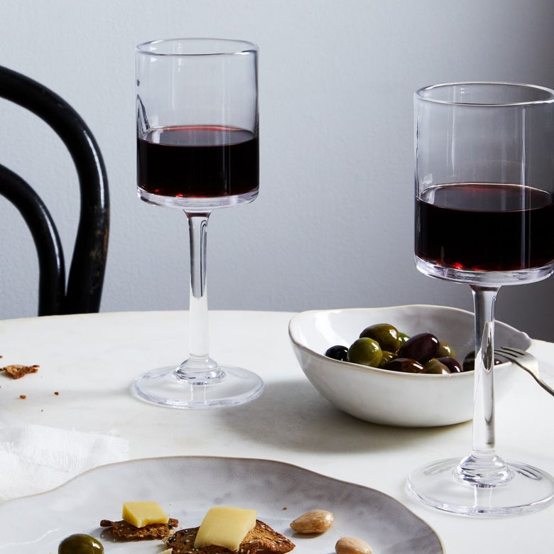 Two glasses of red wine sit beside a bowl of olives and a plate of cheese and crackers on a table