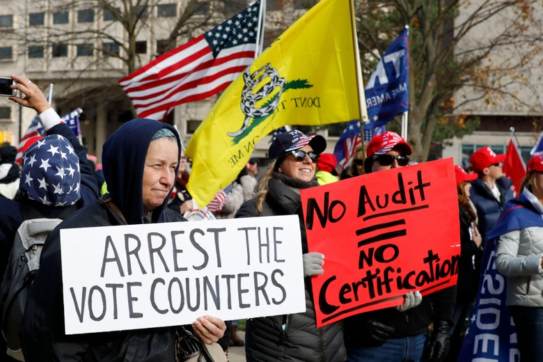 """A crowd of pro-Trump protesters. One person holds a sign that reads """"Arrest the Vote Counters."""" Another holds a sign that reads """"No Audit = No Certification."""""""