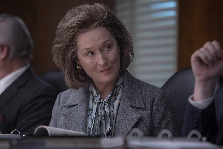Meryl Streep sits at a table, an open binder in front of her.