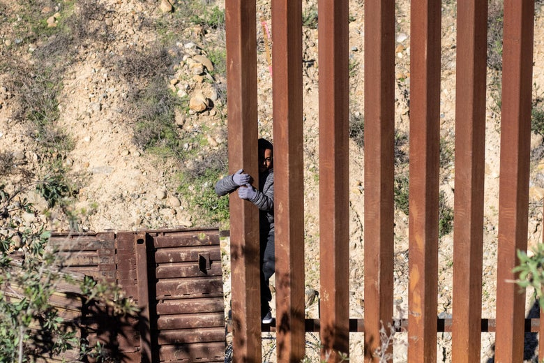 Mexican migrant child Kevin Andres, from Guerrero state, crosses the US-Mexico border fence from Tijuana to San Diego County in the US, as seen from Tijuana, Baja California state, Mexico, on December 28, 2018.