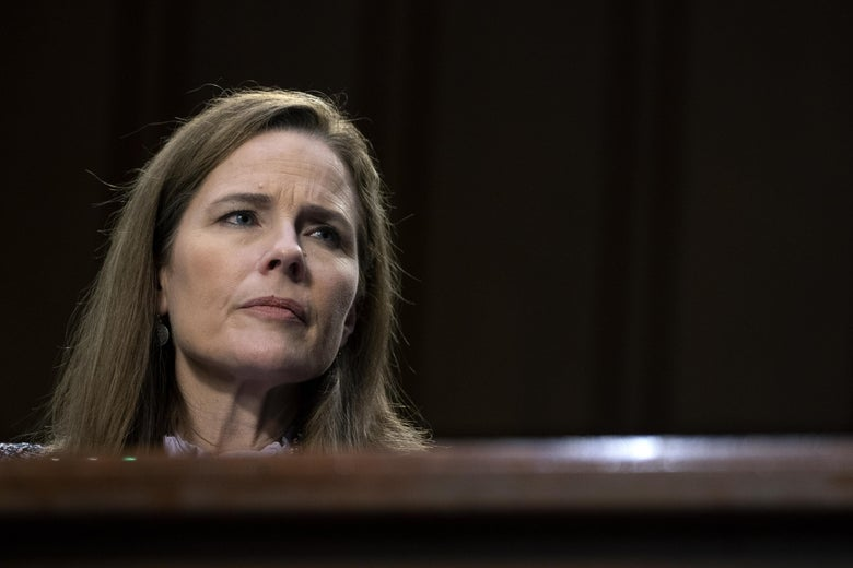Amy Coney Barrett looks to the side.