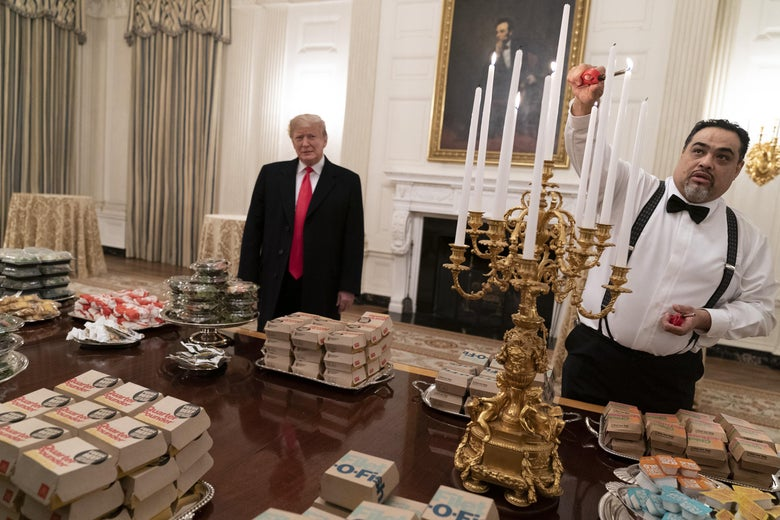 Trump looks awkwardly on as a White House staffer lights an elaborate candelabra over a table full of fast food burgers.
