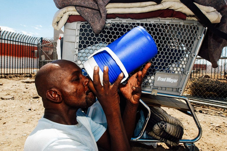 Desmont Smith, who is homeless, sit in the shade of his shopping cart drinking water, near the train tracks in Phoenix where the temperature reached 108 degrees.