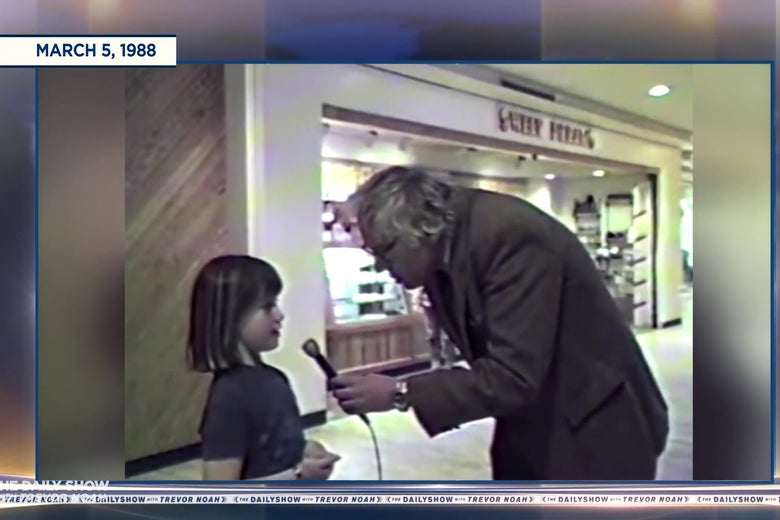 A still from Bernie Sanders' public access show in which he is leaning way over to interview a very short little girl.