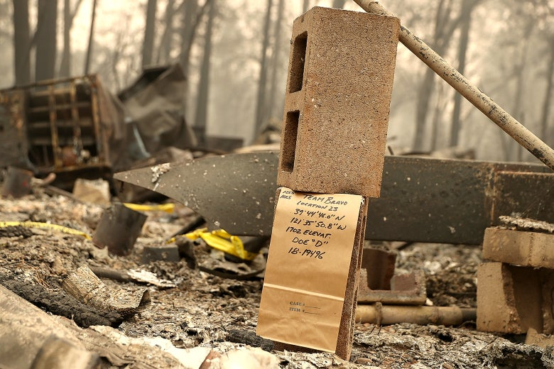 """A note is visible where rescuers found a fire victim at a mobile home park that was destroyed by the Camp Fire on Nov. 14 in Paradise, California. The note, written on a brown paper bag, says """"Team Bravo, Location 23, 39 44' 46.0"""" N, 121 35' 50.8"""" W, 1702 Elevat., Doe """"D"""", 18-19496"""""""