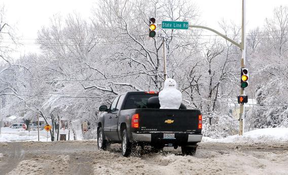 A pickup truck with a snowman in the back drives through the snow on Feb. 26 in Kansas City, Missouri.