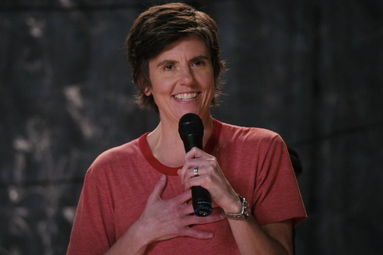 Tig Notaro grins, a hand on her chest as she holds a microphone. She is performing in her new special, Happy to Be Here.