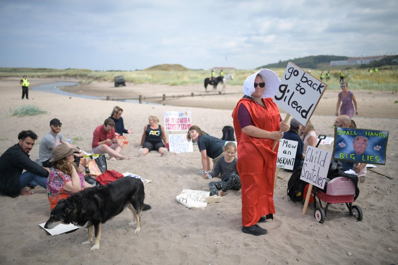 A woman wears a costume in the style of the 'Handmaid's Tale' on the beach as police patrol the area near Trump Turnberry Luxury Collection Resort during the U.S. President's visit to the United Kingdom on July 14, 2018 in Turnberry, Scotland.