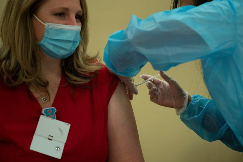 Woman sits to receive COVID vaccine through an injection in her shoulder.