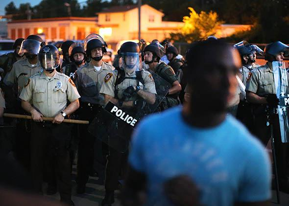 Police stand watch as demonstrators protest the shooting death of teenager Michael Brown.
