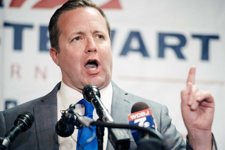 Stewart speaks in front of an array of microphones while wagging his finger.