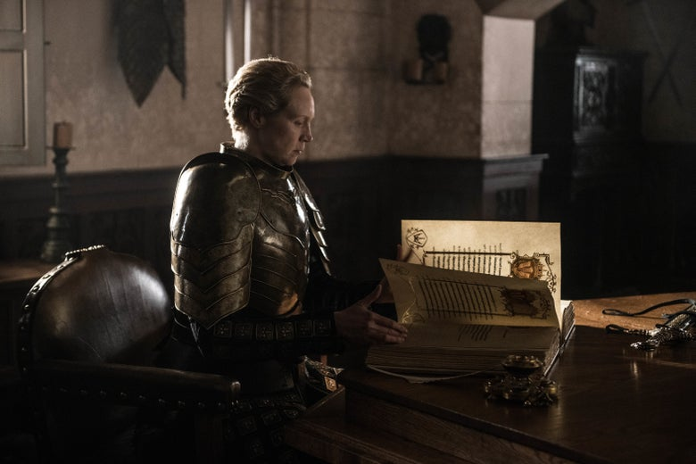 Gwendoline Christine as Brienne sits wearing armor, leaving through a large bound book.
