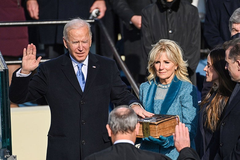 Joe Biden raises his right hand and puts his left hand on the Bible his wife, Jill, is holding as he is sworn in as president.