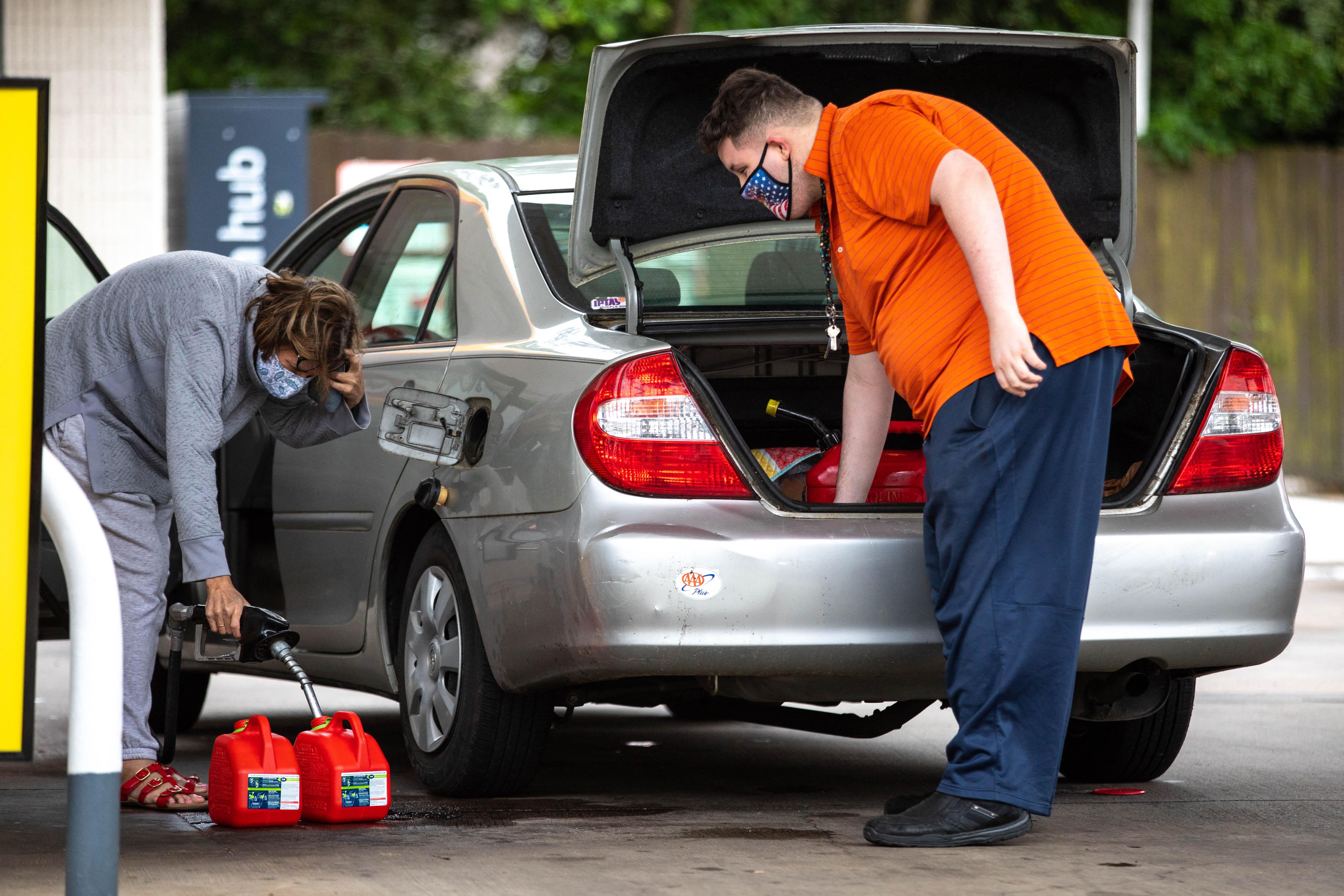 Motorists fill up gas cans at a Shell station in Charlotte, North Carolina on May 12, 2021.