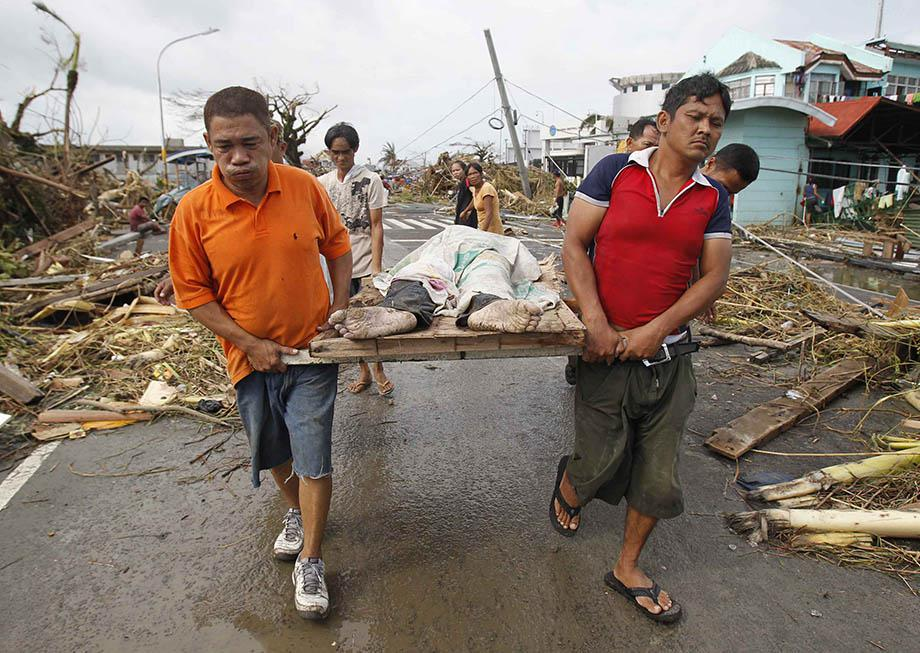 Survivors carry a person killed as super Typhoon Haiyan battered Tacloban city, central Philippines.