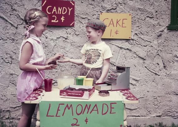 An enterprising young boy sets up a stall selling cake, candy and lemonade to his neighbors, 1955.