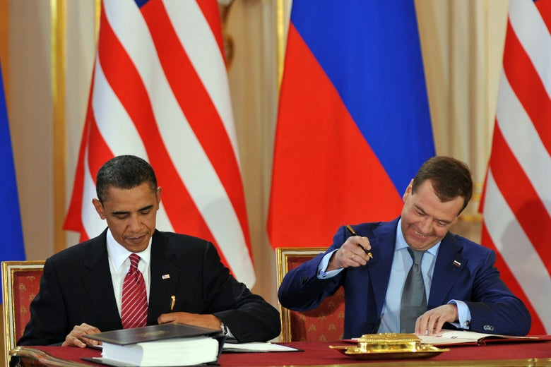 Obama and Medvedev each sign their copy of the treaty, sitting beside each other at a table with American and Russian flags behind them. Medvedev smiles broadly as he puts pen to paper.