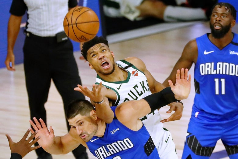 Giannis Antetokounmpo fouls Nikola Vucevic while reaching for a loose ball