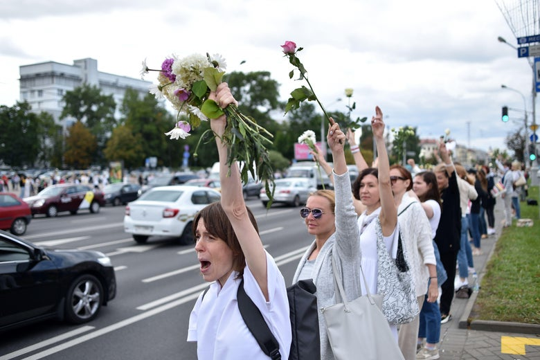 Women wearing white chant slogans as they stand along the side of the street in Minsk.