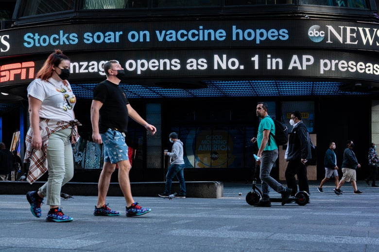 """People in masks walk by an ABC News ticker that says """"Stocks soar on vaccine hopes."""""""