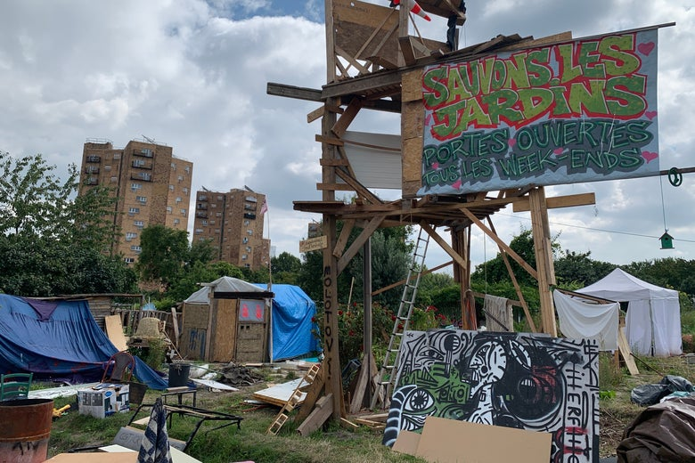 """A makeshift camp of tents with a sign above that says """"Save the Gardens"""" in French"""