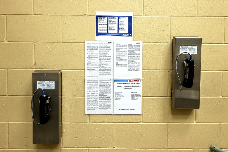 Two staggered pay phones attached to a brick wall.