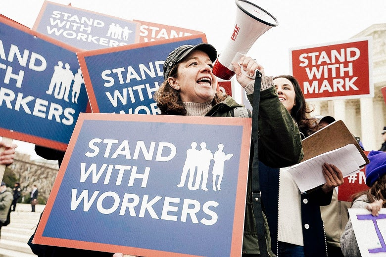 """A woman holds a bullhorn and a sign that says, """"STAND WITH WORKERS."""""""