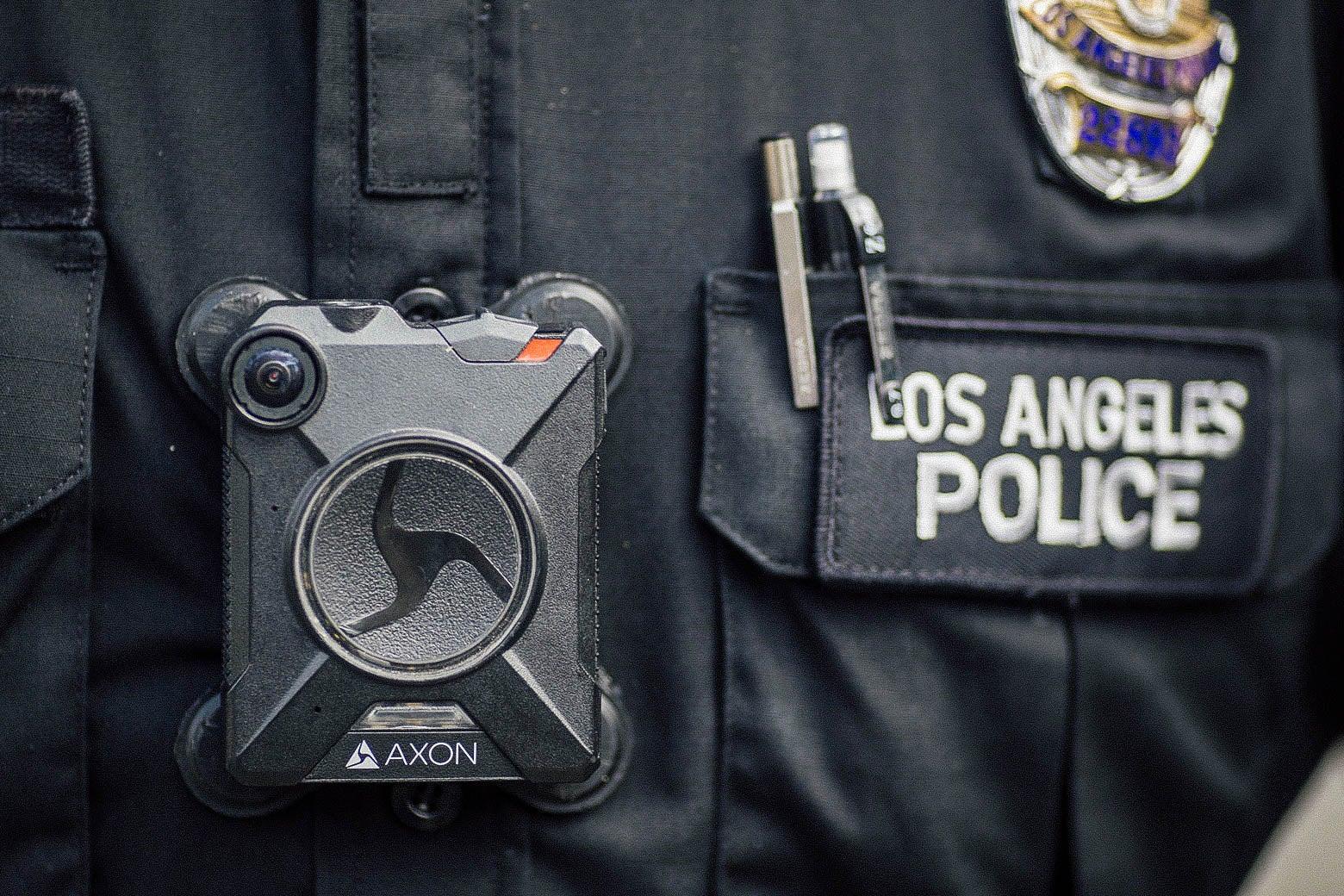 A police officer wears an Axon body camera.