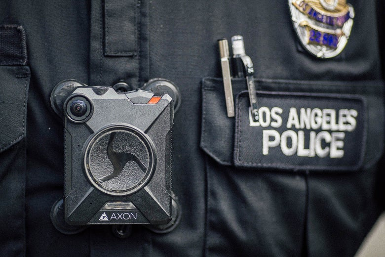 A police officer wears an Axon body camera.