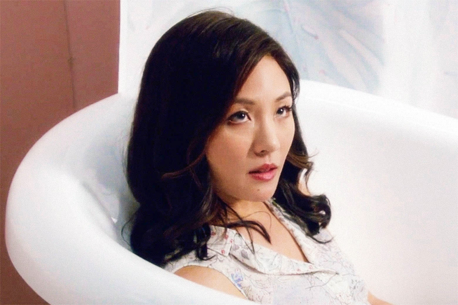 Constance Wu's character in a bathtub on the show.