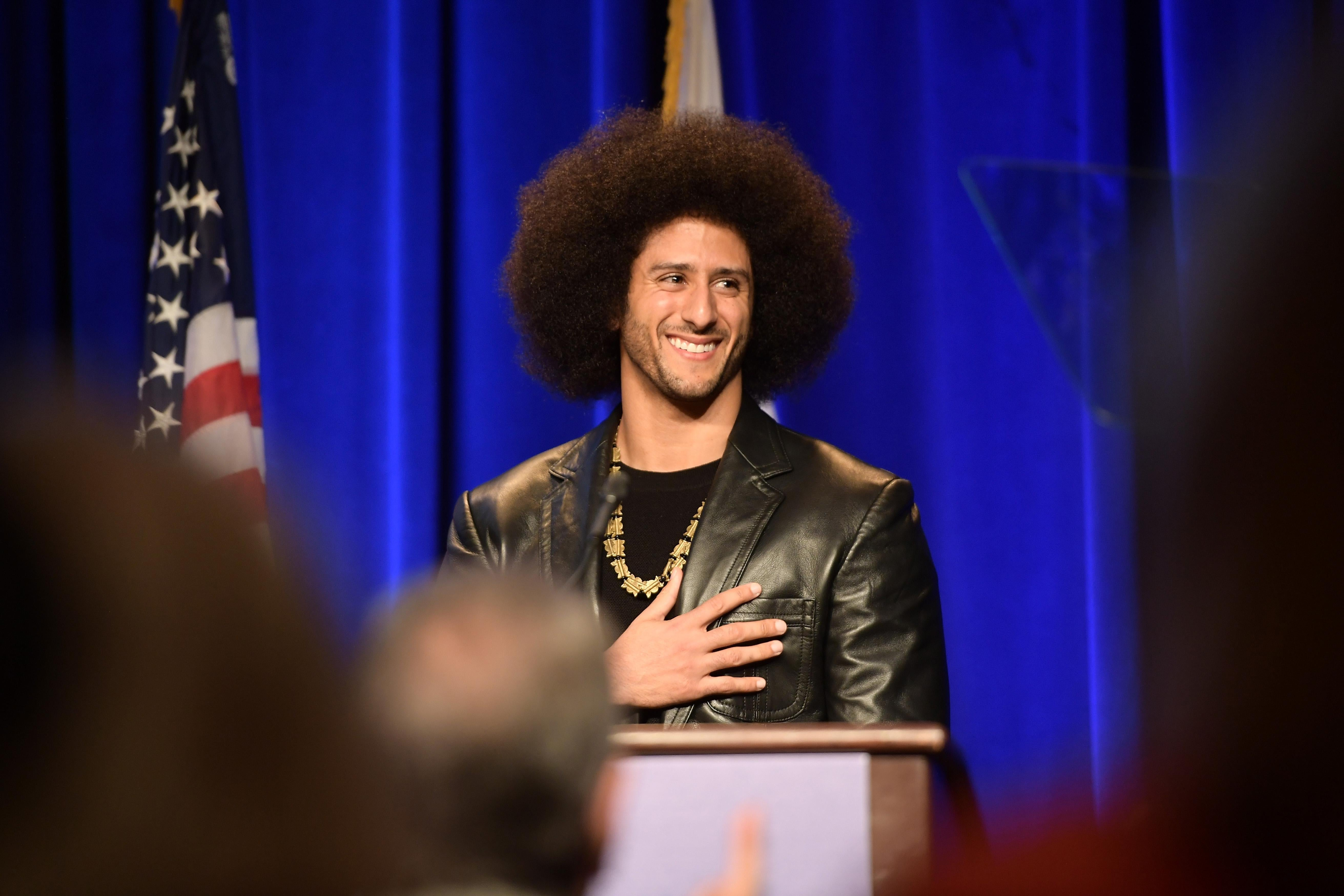 Audience applauds Colin Kaepernick, standing onstage behind a podium.