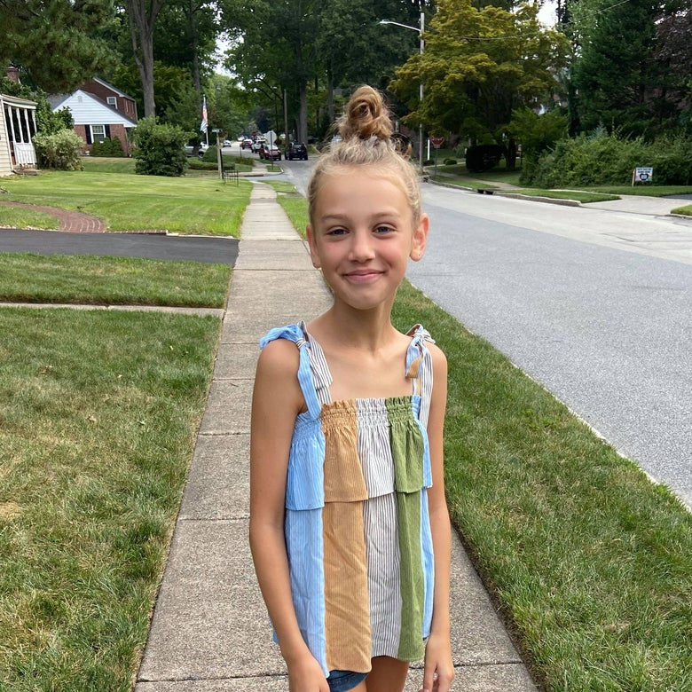 A blond girl smiles while standing on a suburban sidewalk.
