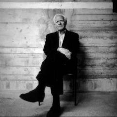 Author John Le Carré sitting in a chair against a wood paneled wall.