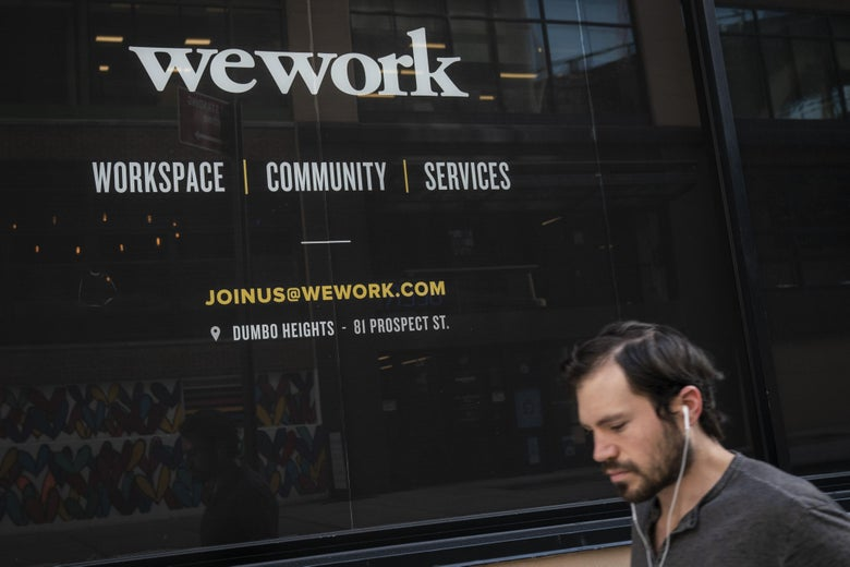 A man with earbuds in walks by the façade of a WeWork building