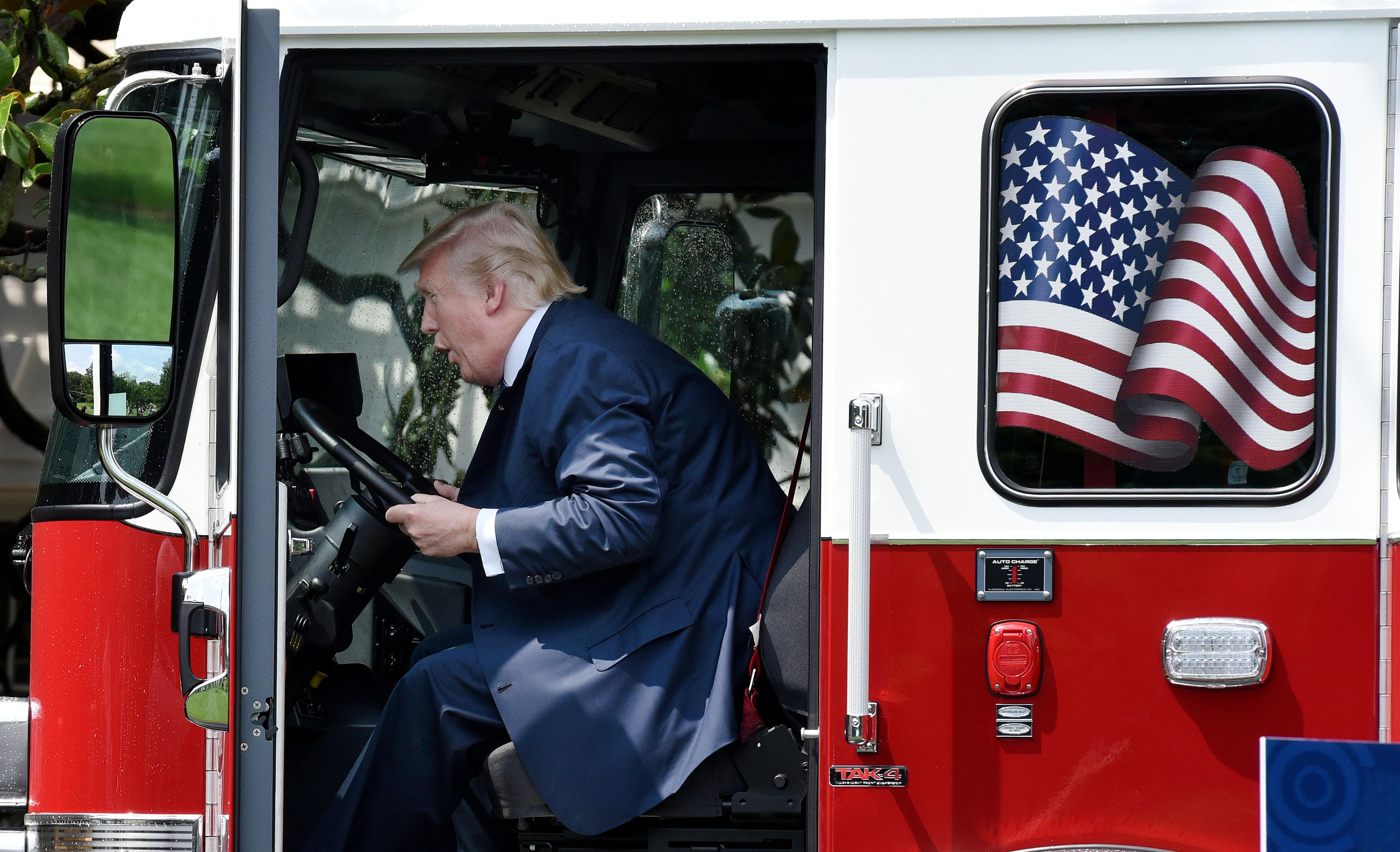 President Trump examines a fire truck from Wisconsin-based manufacturer Pierce on the South Lawn during a 'Made in America' product showcase event at the White House in Washington, DC, on July 17, 2017.  / AFP PHOTO / Olivier Douliery        (Photo credit should read OLIVIER DOULIERY/AFP/Getty Images)