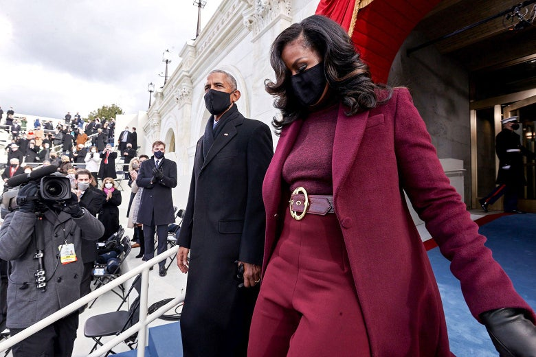 Barack and Michelle Obama arrive at the inauguration. Barack wears a black overcoat, scarf, and mask. Michelle wears a maroon coat with matching pants, sweater, and belt with a large, gold buckle.