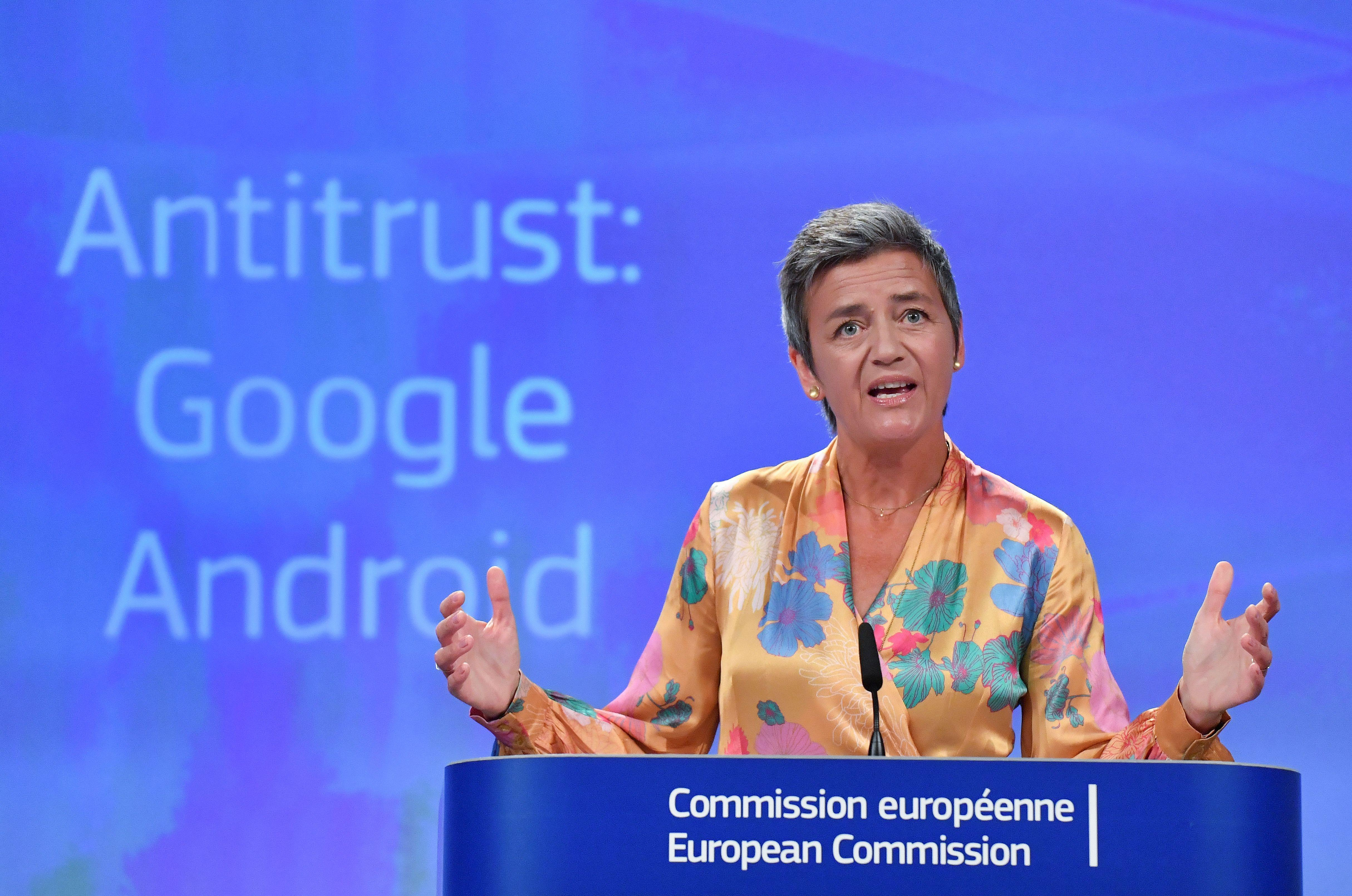 "Margrethe Vestager stands at a podium with the words ""Antitrust: Google Android"" behind her."
