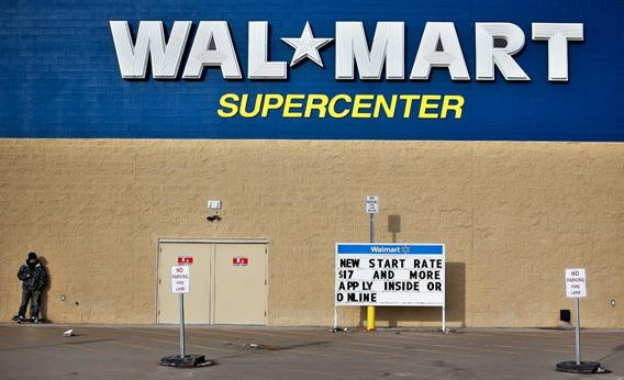 A man stands on a skateboard outside a Wal-Mart store in Williston, N.D., March 13, 2013.